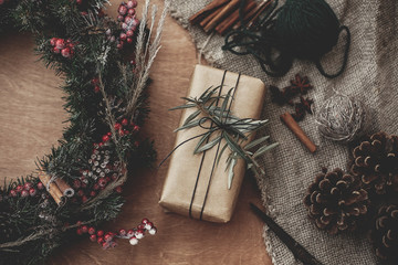Rustic Christmas wreath and stylish craft gift box with green branch at fir, red berries,pine cones,rope, cinnamon, scissors on rustic wood, flat lay. Atmospheric moody image