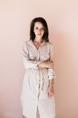 Young beautiful stylish woman posing outdoor in summer. Peach pastel colors.