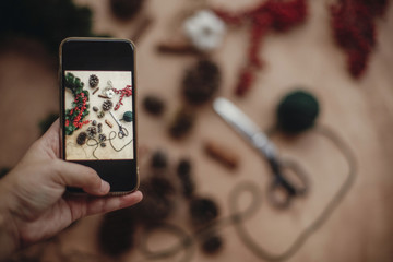 Hand holding phone and taking photo of rustic christmas wreath flat lay. Photo process of making christmas wreath at holiday workshop with fir branches,berries, cones. Copy space