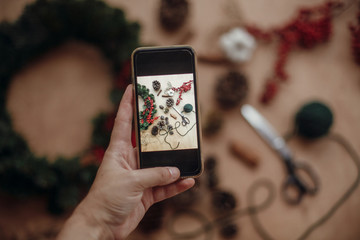 Hand holding phone and taking photo of rustic christmas wreath flat lay. Photo process of making christmas wreath at holiday workshop with fir branches,red berries, pine cones,