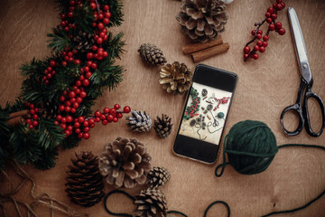 Phone with photo of rustic christmas wreath flat lay. Process of making christmas wreath at holiday workshop with fir branches,red berries, pine cones,thread, scissors, cinnamon, cotton