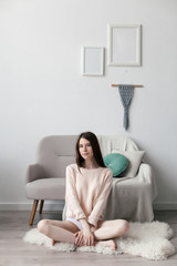 Minimalistic style photo with young brunette woman sitting on the floor at home