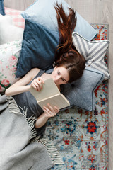 Young brunette woman are lying on the floor at home and reading the book