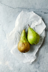 Two Fresh Conference Pears  on white Paper. Flatlay. Food still life