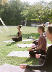 outdoor yoga class on the lawn in the morning with young millenial women meditating