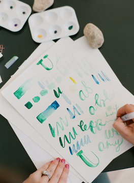 artists practice watercolor painting and hand lettering in outdoor classroom