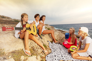 Friends playing musical instruments on the beach