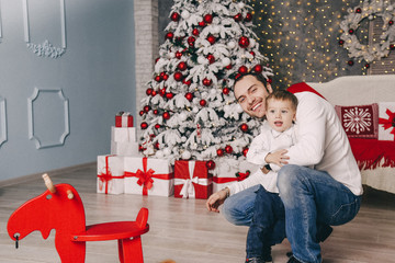 handsome father playing with his small cute son near decorated New year tree