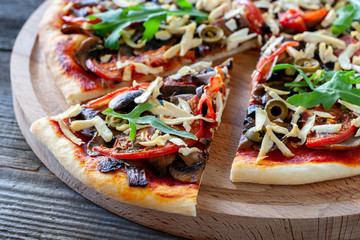 Vegetarian pizza with tofu, mushrooms, tomatoes, olives and arugula. Healthy food.