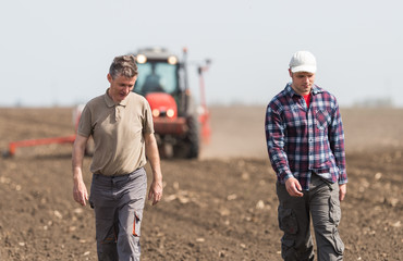 Farmers examing planted wheat fields