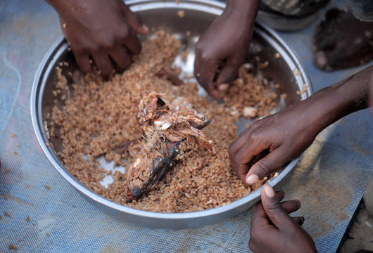 kids eating brown rice and fish in Africa - closeup