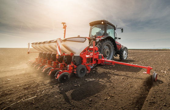 Farmer with tractor seeding sowing crops at agricultural field