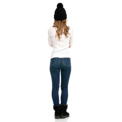 Beautiful woman in sweater jeans hat cold on white background isolation back view