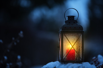 Candle lantern in the snowy garden at dusk.