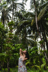 Young lady in dress between tropical forest