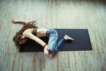 beautiful caucasian woman with long hair and slender body doing yoga on a mat top view