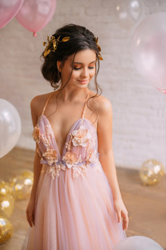 a gorgeous young queen with dark hair and gold in a chic light pink dress with purple color, confusedly lowers her eyes to the floor, stands in a bright spacious room near the balloons