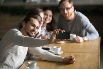 Millennial guy holding smartphone making self-portrait picture at friendly meeting with colleagues in cafe, happy friends smile for selfie sitting at coffee table, student shot photo with cellphone