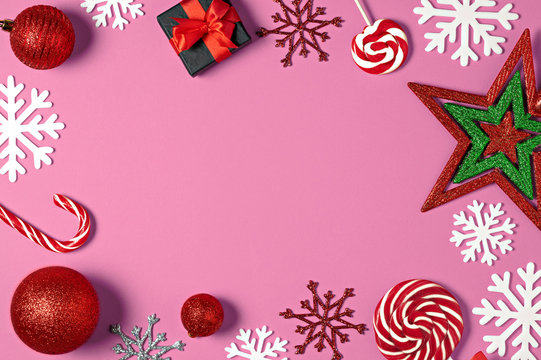 Christmas handmade gift boxes decorated with candy, star, white snowflakes on pink background top view. Merry christmas greeting card. Winter xmas holiday theme. Happy New Year