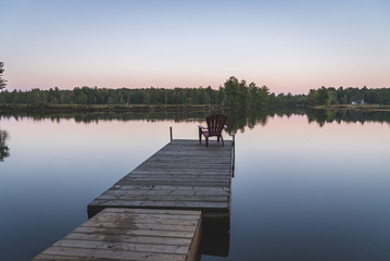 Adirondack chair sitting on a dock - Muskoka, Ontario, Canada.