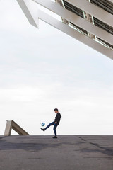 Side view of man playing soccer on street against cloudy sky