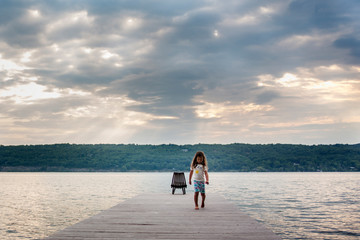 Girl walking on pier over lake against cloudy sky at sunrise