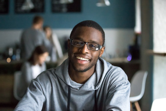 Portrait of smiling African American student looking at camera sitting in cafe, black millennial man posing making picture in coffeeshop, afro male in glasses drinking coffee working in coffeehouse