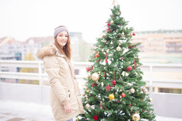 Young woman on balcony near christmas tree