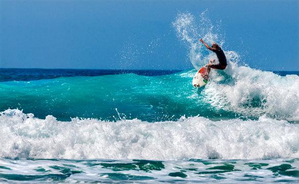 Surferos practicando surfing en las olas.