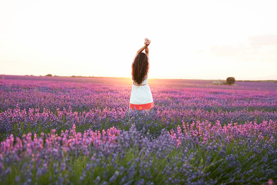 Smiling young woman between violet lavender field