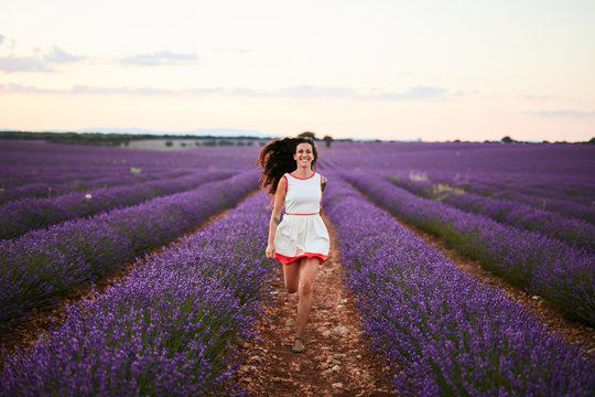 Smiling young woman running between violet lavender field