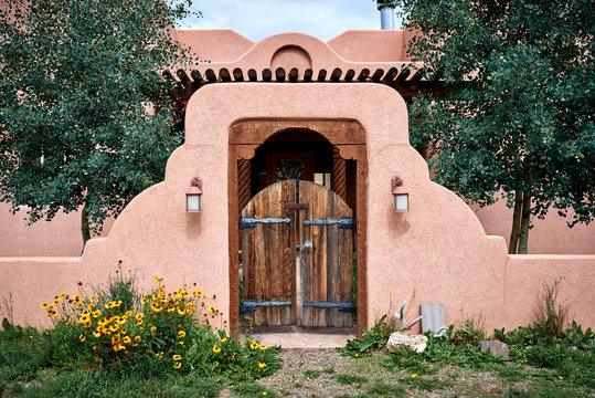 an adobe building with a wooden gate and wall