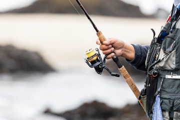 Closeup of mans hand on fishing rod and reel