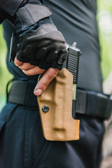 the guy puts the gun in the holster close-up