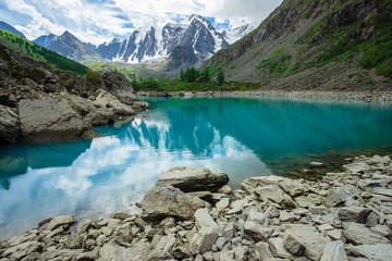 Mountain lake is surrounded by large stones and boulders on front of giant beautiful glacier. Amazing snowy mountains. Ridge with snow. Wonderful atmospheric landscape of majestic nature of highlands.