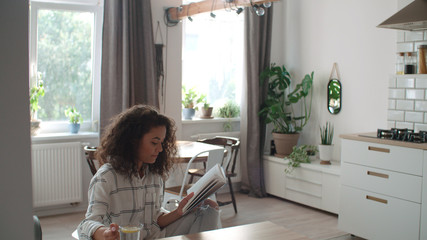 Beautiful Afro American woman reading book at home.