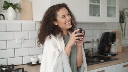 Portrait of smiling woman drinking coffee or tea at home.