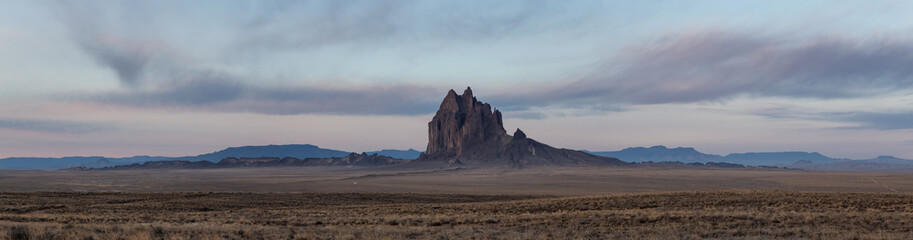 Wall Mural - Dramatic panoramic landscape view of a dry desert with a mountain peak in the background during a vibrant cloudy sunrise.Taken at Shiprock, New Mexico, United States.