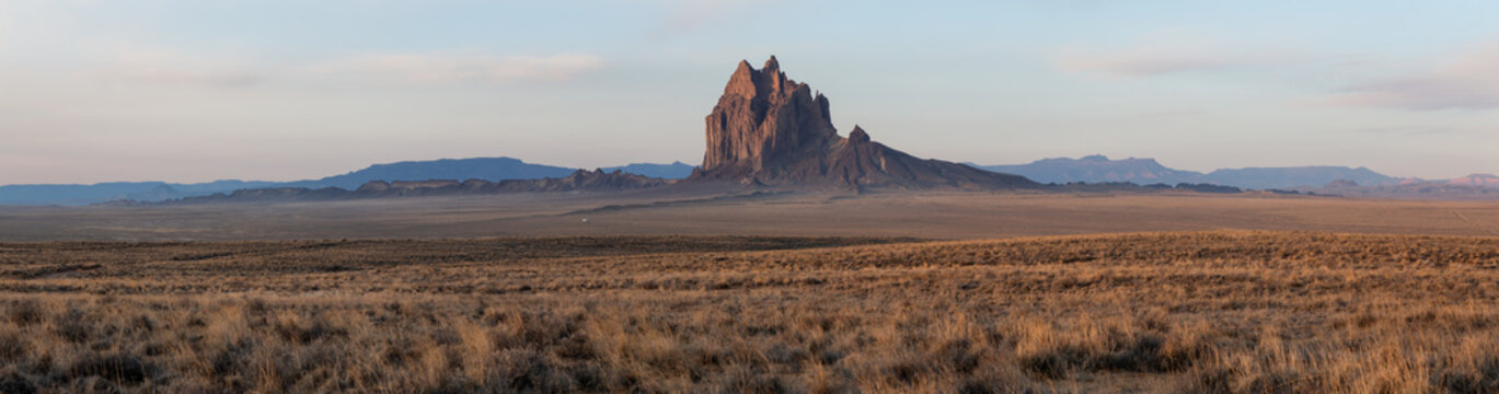 Dramatic panoramic landscape view of a dry desert with a mountain peak in the background during a vibrant cloudy sunrise.Taken at Shiprock, New Mexico, United States.