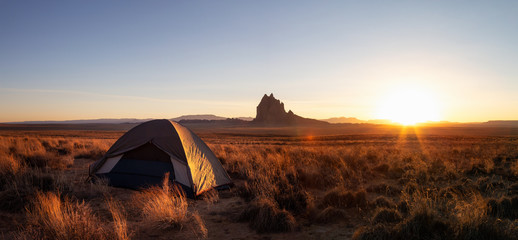 Striking panoramic landscape view of a tent in the dry desert with a mountain peak in the background during a vibrant sunset. Taken at Shiprock, New Mexico, United States.