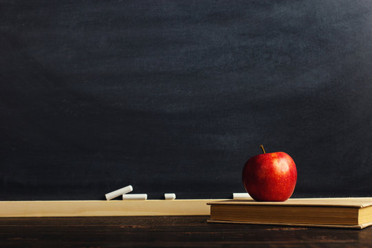 Black chalk board over wooden table with a book and an apple, blank for text or background for a school theme.