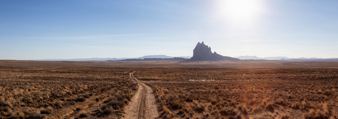 Striking panoramic landscape view of a dirt road in the dry desert with a mountain peak in the background. Taken at Shiprock, New Mexico, United States.