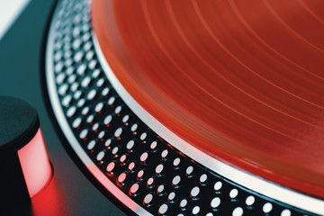 Vinyl record closeup. A ray of light on a piece of vinyl. Turntable player. Sound technology for DJ to mix and play music. Red vinyl. The texture of the bands on the vinyl record. Turntable player