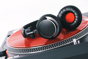 Vinyl record player turntable and black headphones on a white background. Equipment for the disc jockey. Sound technology for DJ to mix and play music. Red vinyl plate. Vinyl player