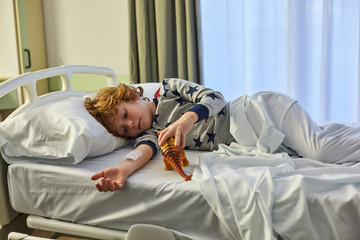 Child patient lying on a hospital bed and playing with a figure toy