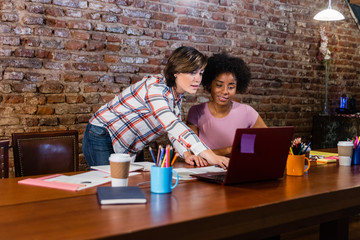 Business women working at laptop in conference table