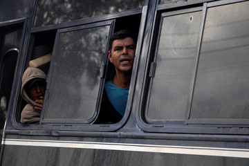 A migrant, part of a caravan of thousands from Central America trying to reach the United States, peers from a bus window before being transferred to a new shelter in Tijuana