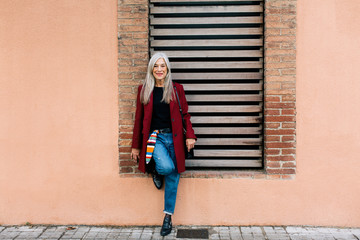 Mature woman with grey long hair standing on the street in winter.