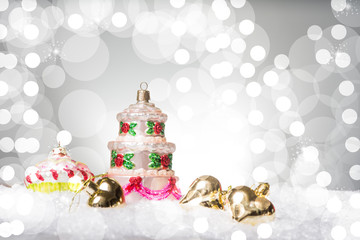 Christmas decoration with the shape of a multi floor wedding cake,  on snow, against a beautiful holiday inspired background, copy space left