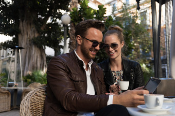 Loving couple watching smartphone in cafe